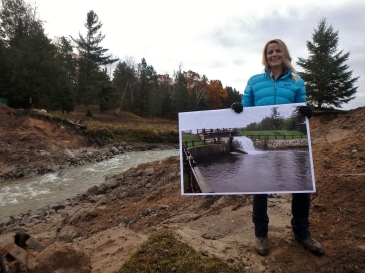 """Huron Pines Associate Director Lisha Ramsdell proudly shows the dramatic difference with a """"before"""" photo of the dam"""